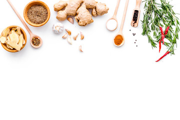 Seasoning background. Dry spices near ginger, garlic, rosemary, chili on white background top view copy space Wall mural