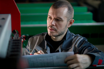 Man worker repairman engineer during work - reads paper plan