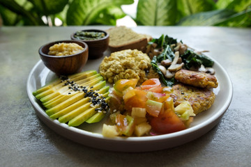 Vegan tofu with avocado, bread, vegetables and source close-up on a plate. Concept of eco healthy diet