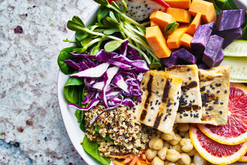 colorful buddha bowl close up with grilled tofu