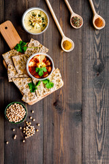 Serve hummus. Bowl with dish near pieces of crispbread on dark wooden background top view copy space