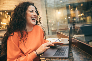 attractive laughing girl in a cafe using a laptop. Lush beautiful hair. Online communication online dating. Fun jokes