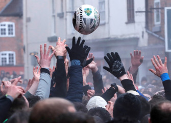 Players scrabble for the ball during the annual Ashbourne Royal Shrovetide Football match in Ashbourne