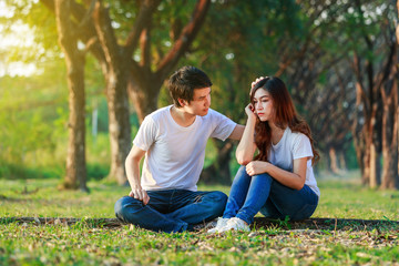 unhappy woman sitting with a concerned guy comforting her in park