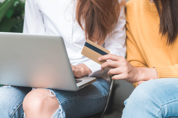 Close up of a couple young Asian women using her credit card while they do shopping online with her laptop. Young women shopping online in the garden holding her credit card. Shopping online concept.