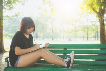 Happy hipster young asian woman writing into her diary in park. Happy hipster young asian woman working on notebook in park. Student studying outdoors. Lifestyle woman outdoor concept. Flare light.