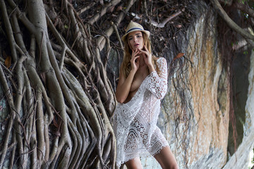 Beautiful young sexy lady with curly blond hair and passion lips in a white transparent knitted lingerie and stylish hat hot posing on fairy background tree roots. Fashion summer photo shooting model