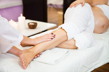 Young pregnant woman relaxing with hand leg massage at beauty spa salon. Close-up.  Spa treatment