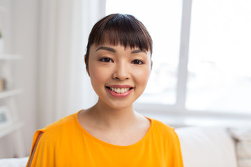 portrait of smiling young asian woman at home