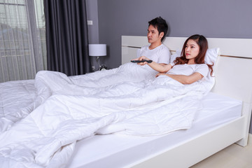 young couple lying on a bed with remote control and watching television in bedroom
