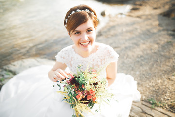 Gorgeous beautiful bride smiles while posing by the river with bouquet