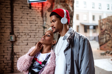 Attractive mulatto woman and her dark skinned stylish friend who listens music with headphones, walk together in street, looks at something with thoughtful expression. People and lifestyle concept.