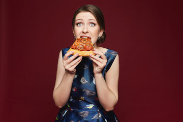 Beautiful and fashionable brunette model girl in blue dress eating pizza, isolated at vinous background, indoors