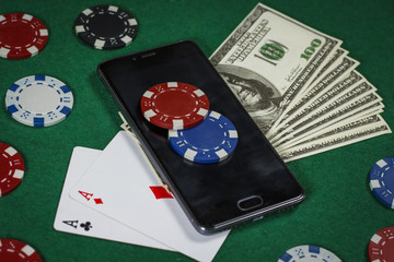 Poker chips, phone and cards on the green table