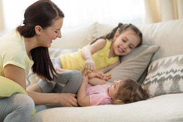 Smiling kids and their mom having a fun pastime on sofa in living room at home