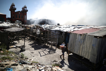 A woman walks carrying goods next to the Marche Hyppolite (Hyppolite Market), also known as Marche en Fer (Iron Market), after a fire that affected part of the market and the surrounding stands in Port-au-Prince
