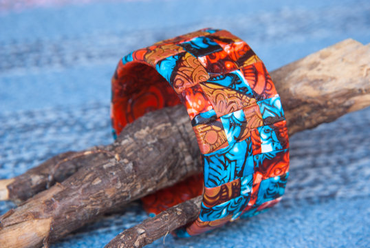 Ethnic jewellery bracelet on Blue fabric. Handmade jewelry bracelet of polymer clay.Fashion background with bagle bracelet.Hobby, handicraft, mosaic