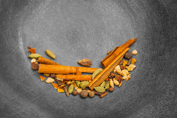 Seasonings for the preparation of mulled wine, cinnamon, cardamom, orange, pepper. on a dark gray metallic background