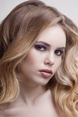 Portrait of blonde girl with makeup and hairstyle from curly hair on grey background close-up