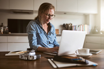Young woman working online with a laptop in her kitchen