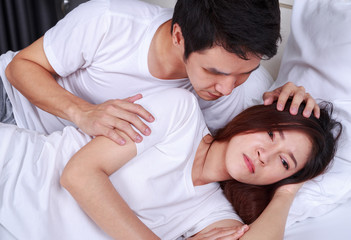 unhappy woman lying on bed with a concerned guy comforting her
