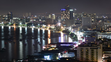 The bay and skyscrapers in twilight time and midnight time in Pattaya, Thailand. Pattaya city is famous for sea sport and night life entertainment.