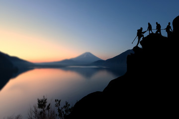 Male and female hikers climbing up silhouette mountain cliff and one of them giving helping hand. helping and, team work concept.