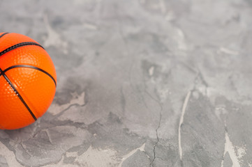 One new orange soft rubber basketball ball on old worn cement