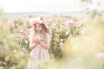 Cute kid girl 4-5 year old holding flower standing in rose field. Wearing stylish dress and floral wreath outdoors. Spring season. Wall mural