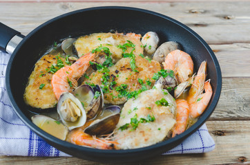 Hake with prawns and clams in frying pan.