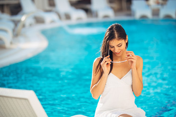 Attractive young woman relaxing at .luxury vacation resort pool.Enjoying summer.Vacation mood.Girl at travel spa resort pool.Flirting female.Traveling alone,pampering.Summer tan,body.Stress free mood