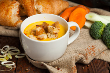 Pumpkin and carrot soup with cream and parsley on dark wooden background.