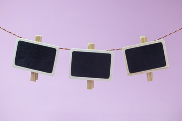 Clothes pegs with blank small blackboards against rose background