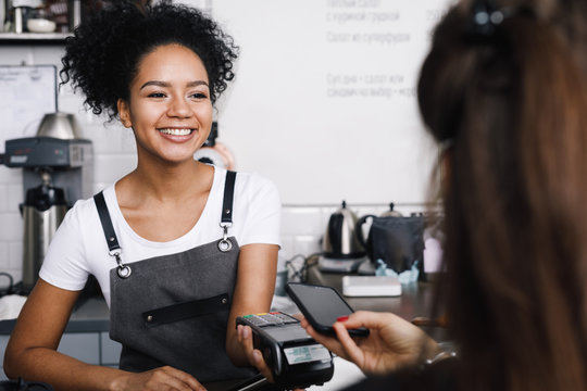Customer paying with her mobile phone at a small cafe