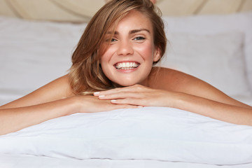 Horizontal shot of pleased young female model with broad smile, enjoys rest during weekend, lies on comfortable white bed, expresses positiveness. Comfort, good morning and relaxation concept