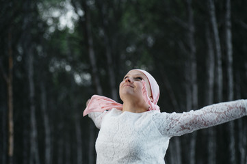 woman with pink headscarf in the forest, has cancer