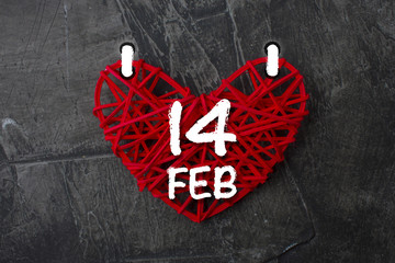 sheet of a calendar with the date of Valentine's Day in the form of red hearts on a dark background. Love theme