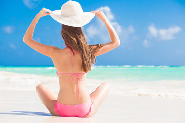 back view of woman in bikini relaxing at white sand beach