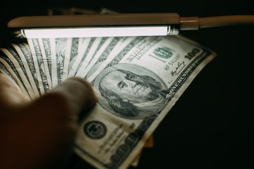 Man hand with a stack of hundred US dollars bills over banknote detector lamp, close up