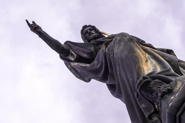 Diagonal position of Statue, hands indicates free space. Sculpture of St. John the Baptist on the Charles Bridge in Prague in the Czech Republic.