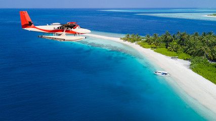 Seaplane flying above exotic iceland in Maldives.