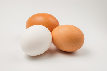 Two brown and single white chicken eggs on a white surface.