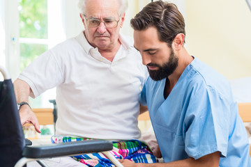 Altenpfleger hilft Senior aus dem Bett in den Rollstuhl