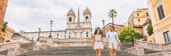 Luxury Europe travel couple on honeymoon vacation walking down Spanish steps stairs in Rome, Italy. European cruise destination italian summer holiday tourists horizontal banner panorama.