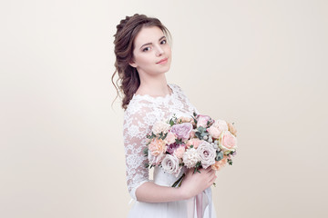 Beautiful girl holding a bouquet of flowers wearing in luxurious wedding dress isolated on background