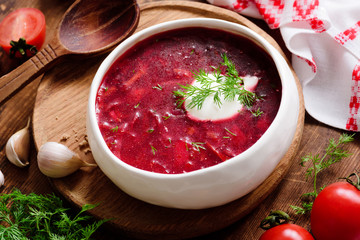 Borscht soup in white bowl with sour cream. National Ukrainian and Russian cuisine food. Closeup view