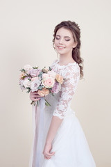 Attractive smiling woman holding a bouquet of flowers wearing in luxurious wedding dress isolated on background