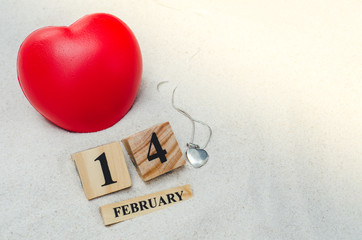 February 14, wooden calendar with red heart shape and siver locket on sand background