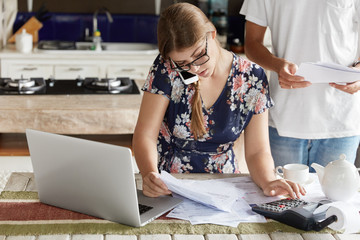 Indoor view of beautiful woman plans family budget, calculates figures and works with documentation, has busy telephone conversation, sits in front of opened laptop at kitchen table, man stands behind