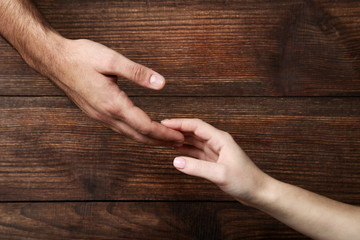Female and male hand holding each other on brown background